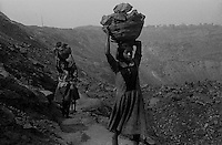 Children bringing out coal from an open cast pit at Jharia. Unemployment, Poverty bringing in crime in the coal fields of India. Children are involved in pilfering of coal. Bhagatdih Colliery, Jharia, Jharkhand, India. Arindam Mukherjee