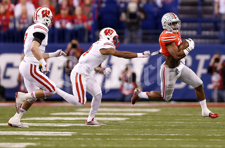 Ohio State Buckeyes running back Ezekiel Elliott (15) dodges a tackle from Wisconsin Badgers cornerback Devin Gaulden (4) in the first quarter of the Big Ten Championship game between the Ohio State Buckeyes and the Wisconsin Badgers at Lucas Oil Stadium in Indianapolis, Saturday night, December 6, 2014. (The Columbus Dispatch / Eamon Queeney)