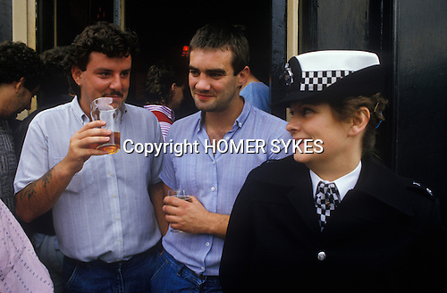 Two male Chelsea football fans having a pint before the game, flirting with an attractive female police woman. London. UK