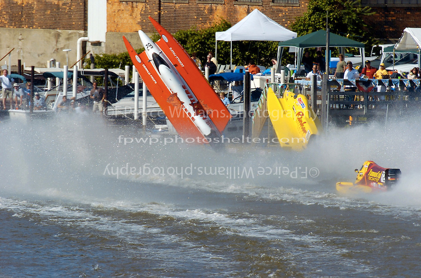 2004 Bay City River Roar, Bay City, Michigan, 26-27 June, 2004..Frame 1:.Chris Fairchild (L, #62) and Terry Rinker (R,#10) come together during the inverted start for Saturday's 2 heat race. Both boats suffer a blowover, Fairchild's boat landing upside down in the river only to be run over by Todd Bowden. During Rinkers crash, his boat snagged a pier with the lower unit, ripping it away. The boat continued skyward, hitting the staircase from the lower to the upper pier and then striking a piling with the right rear of the hull, with that large chunk falling to the pier below (to be seen in a later picture. Rinker continued his backflip, finally landing just a few feet from a docked pleasure boat filled with spectators. No one was injured in the accident and both drivers made the restart in their backup boats...©F. Peirce Williams 2004..F. Peirce Williams .photography.P.O. Box 455 Eaton, Ohio 45320 USA.p: 317.358.7326 e: fpwp@mac.com