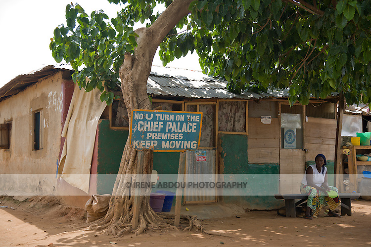 "A woman lounges in front of this Chief's Palace in the Durumi area of Abuja, Nigeria.  The sign reads, ""No U Turn on the Chief Palace Premises Keep Moving."""