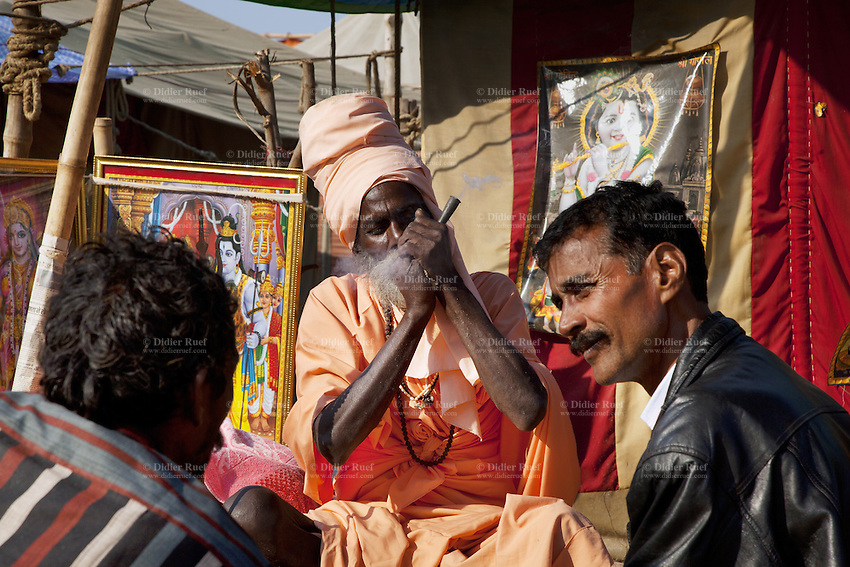 "India. Uttar Pradesh state. Allahabad. Maha Kumbh Mela. A Sadhu sits and smokes a shilom with hashish outside his tent in Sangam. Both men are visitors and wait to smoke the drug. Two drawings, one of Shiva (left) and Krishna (right). Shiva is a Hindu deity. Krishna is another Hindu deity, one of the ""avatars"" (or ""incarnation"") of Vedic Supreme God Vishnu or Narayana. The Kumbh Mela, believed to be the largest religious gathering is held every 12 years on the banks of the 'Sangam'- the confluence of the holy rivers Ganga, Yamuna and the mythical Saraswati. In Hinduism, Sadhu (good; good man, holy man) denotes an ascetic, wandering monk. Sadhus are sanyasi, or renunciates, who have left behind all material attachments. They are renouncers who have chosen to live a life apart from or on the edges of society in order to focus on their own spiritual practice. A Sadhu is usually referred to as Baba by common people. The Maha (great) Kumbh Mela, which comes after 12 Purna Kumbh Mela, or 144 years, is always held at Allahabad. Uttar Pradesh (abbreviated U.P.) is a state located in northern India. 10.02.13 © 2013 Didier Ruef"