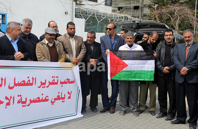 """Palestinians hold banners during a protest against the U.N. Secretary-General Antonio Guterres decision to remove Israeli 'apartheid' report from Economic and Social Commission for Western Asia (ESCWA) website, in front of the headquarter United Nation """"UNSCO"""", in Gaza city on March 21, 2017. U.N. Under-Secretary General and ESCWA Executive Secretary Rima Khalaf resigned after saying she was pressured to withdraw a controversial report that accused Israel of establishing an """"apartheid state."""". Photo by Ashraf Amra"""