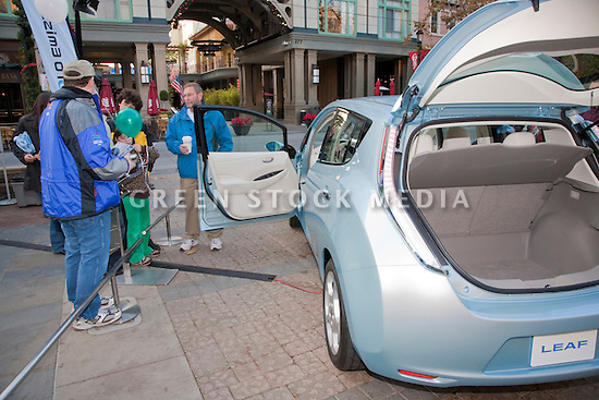 Crowd looking at new Nissan Leaf zero emission electric car. Nissan Leaf Zero Emission Tour promotional event for the Nissan Leaf electric car that is scheduled to be released in Fall 2010. Car specs from Nissan: 5 person capacity, 90 MPH top speed, lithium-ion battery, 100 mile average range per charge. Santana Row, San Jose, California, USA, 12/5/09