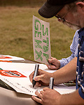 May 5, 2018. Fayetteville, North Carolina.<br /> <br /> Mike Watters makes a sign about GenX contamination at a rally about the GenX pollution of the Cape Fear River on Hwy. 87 just outside the Chemours plant which has been dumping GenX unregulated into the river for years. <br /> <br /> The Chemours Company, a spin off from DuPont, manufactures many chemicals at its plant in Fayetteville, NC. One of these, commonly referred to as GenX, is part of the process of teflon manufacturing. Chemours has been accused of dumping large quantities of GenX into the Cape Fear River and polluting the water supply of city's down river and allowing GenX to leak into local aquifers.