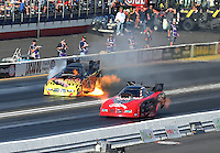 Feb 13, 2016; Pomona, CA, USA; NHRA funny car driver James Campbell (far) explodes an engine on fire alongside Gary Densham during qualifying for the Winternationals at Auto Club Raceway at Pomona. Mandatory Credit: Mark J. Rebilas-USA TODAY Sports