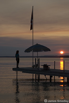 Woman on dock at sunset