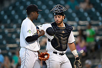 Catcher Scott Manea (25) hands the ball to Tony Dibrell (8) after the pitcher tied a Fireflies single-season strikeout record on Tuesday, August 28, 2018, at Spirit Communications Park in Columbia, South Carolina. Dibrell went on to break the record at 138. Columbia won, 11-2. (Tom Priddy/Four Seam Images)