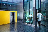 Laboratory workers enter a lift by the entrance to the storage facility in The Wellcome Trust Millennium Building at the Millennium Seed Bank at Wakehurst Place in West Sussex. The building houses facilities for seed-preparation, laboratories and public exhibitions. The large storage vault lies underneath the building. The Millennium Seed Bank Partnership is coordinated by Kew Gardens and aims to collect seeds from every wild plant in the world to insure against extinction. It reached its target of banking seeds from all of the UK's native plant species as well as banking 10% of the world's wild plant species in 2009, and aims to have 25% by 2020.
