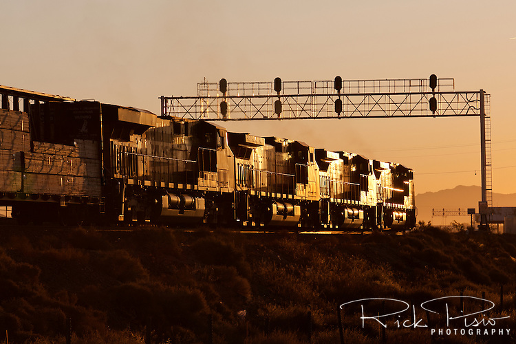 A BNSF freight train heads east into the sunrise out of Barstow, California. Barstow is the site of a large rail classification yard which belongs to the BNSF Railway