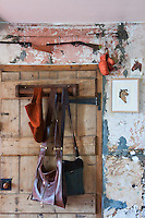A selection of their handmade leather bags hangs on the back of the kitchen door of the restored Victorian farmhouse of designers Jax and Matt Fothergill