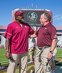Florida State interim head coach Odell Haggins greets Louisiana Monroe head coach Matt Viator before an NCAA college football game in Tallahassee, Fla., Saturday, Dec. 2, 2017. Haggins took over the head coaching duties for Florida State's last football game after Jimbo Fisher left to be the head coach at Texas A&M. (AP Photo/Mark Wallheiser)