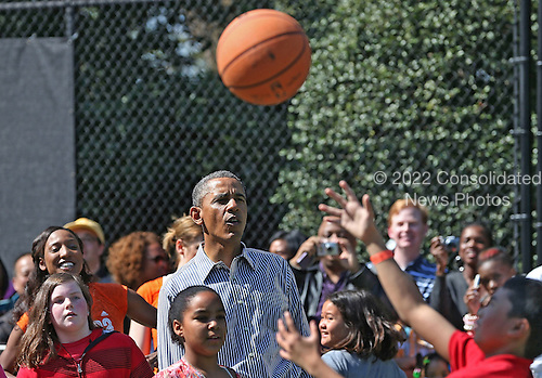United States President Barack Obama watches as children play basketball during the annual Easter Egg Roll on the White House tennis court April 1, 2013 in Washington, DC. Thousands of people are expected to attend the 134-year-old tradition of rolling colored eggs down the White House lawn that was started by President Rutherford B. Hayes in 1878. .Credit: Mark Wilson / Pool via CNP