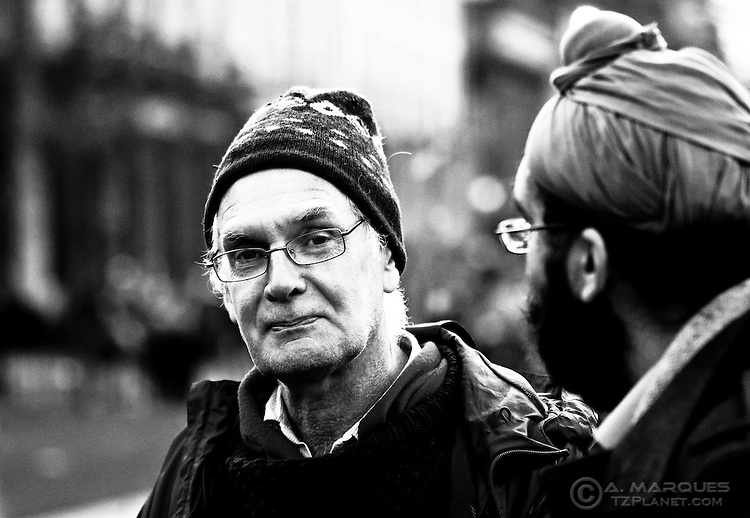 "One of the many people hanging around the Occupy Edinburgh camp. I ended up not talking with him, so I can't tell if he is one of the ""campers"" or is there just to show support.  .I saw this man talking to the other one (on the right) and I wanted to capture his expression looking directly at the lens. I raised the camera and was there maybe 15-20 seconds waiting before he looked straight at the lens - Success."
