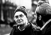 """One of the many people hanging around the Occupy Edinburgh camp. I ended up not talking with him, so I can't tell if he is one of the """"campers"""" or is there just to show support.  .I saw this man talking to the other one (on the right) and I wanted to capture his expression looking directly at the lens. I raised the camera and was there maybe 15-20 seconds waiting before he looked straight at the lens - Success."""