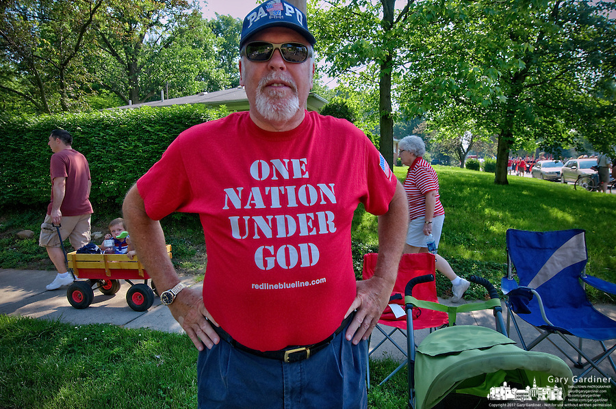 "A man standing with his hands on hips wearing a t-shirt with ""One Nation Under God"" printed on it while watching the Memorial Day parade through Uptown Westerville"