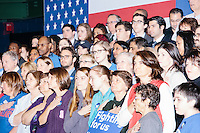 People stand for the National Anthem before as former Secretary of State and Democratic presidential candidate Hillary Rodham Clinton speaks at a rally at Nashua Community College in Nashua, New Hampshire, on Tues. Feb. 2, 2016. Former president Bill Clinton also spoke at the event. The day before, Hillary Clinton won the Iowa caucus by a small margin over Bernie Sanders.