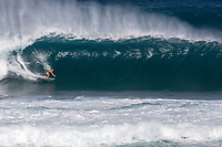 Surfer getting barrelled  on a big wave at Pipeline, North Shore, Oahu