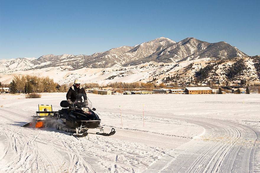 A man grooms a cross-country ski trail with the Bridger Mountains in the distance in Bozeman, Montana.