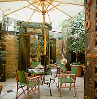 A parasol provides shade for a glass table and green director's chairs in this walled patio garden