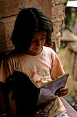 San Ignacio, Peru. Young girl reading a school textbook teaching her English with light from the door.