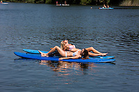 Two attractive, fit women sunbathing on SUP stand-up paddle boards at a secret cove on Lady Bird Town Lake.