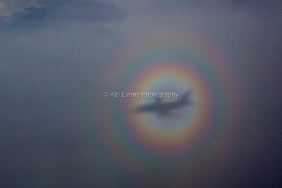 A rainbow encircles a plane.