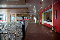 A worker stands inside an empty fastfood restaurant in a reststop in Zhejiang Province, China.