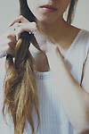 Faceless portrait of a girl braiding her hair