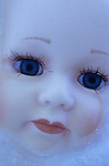 Face of modern toy doll with big blue eyes and long eyelashes lying in sheet of ice