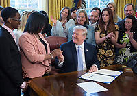 United States President Donald. J. Trump hands Yvonne Ambrose the pen used to sign H.R. 1865, the &quot;Allow States and Victims to Fight Online Sex Trafficking Act of 2017&quot; at The White House in Washington, DC, April 11, 2018. With Trump are victims and family members of victims of online sex trafficking and members of Congress who helped pass the bill. <br /> CAP/MPI/CNP/RS<br /> &copy;RS/CNP/MPI/Capital Pictures
