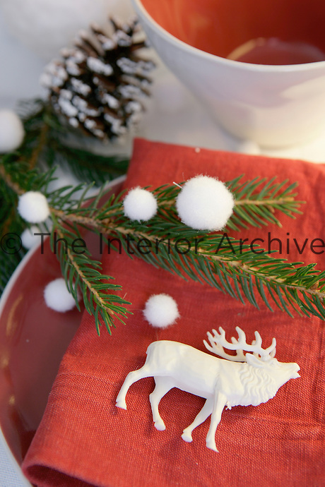 Detail of a place setting on a Christmas table with a little white reindeer on a red napkin