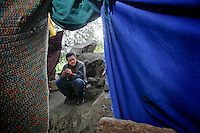 A man originally from the state of Sinaloa waits for a friend to return to their makeshift refuge in a canyon overlooking the fence that separates Mexico from the United States. The 44-year-old man, who declined to give his name, has lived in the United States for over a decade and was deported in early November of 2012 after his place of employment was raided by immigration officers. He was deported to the state of Tamaulipas. He has tried to return to his home and family in East Los Angeles 14 times since late November but has been caught by the border patrol. He now lives in this makeshift tent and hopes to return to his family in the near future. He works as a day laborer and a carpenter in the city of Tecate  whenever he is able to find work. He used to be a carpenter in Los Angeles...Tecate, Baja California, Mexico - February 8, 2013.  (Javier Manzano / For The Washington Post).