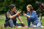 Couple having picnic, laughing, toasting with wine