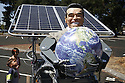 Two young children look at a solar powered chariot driven by a robot holding a planet earth globe and wearing an Arnold Schwarzenegger mask. Contact Green Stock Media to view additional images from this photo shoot. ..Image size: 4368 x 2912 pixels, very high resolution, 12.8 megapixels