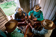 Cuba, March 1992: Tobacco farmers take a rare moment of rest after lunch, playing a game of domino near Vinales, Cuba.