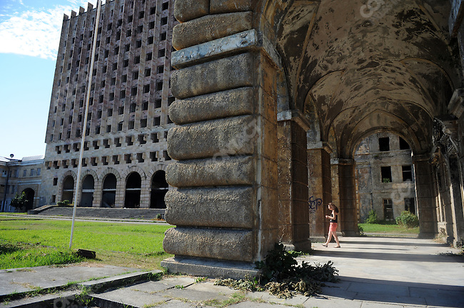 In central Sukhumi, the capital of Abkhazia, a woman walked through the shell of the former government building that was burnt during the separatist conflict with Georgia in 1992-3 and which remains the starkest reminder in the city of the war. August 23, 2011