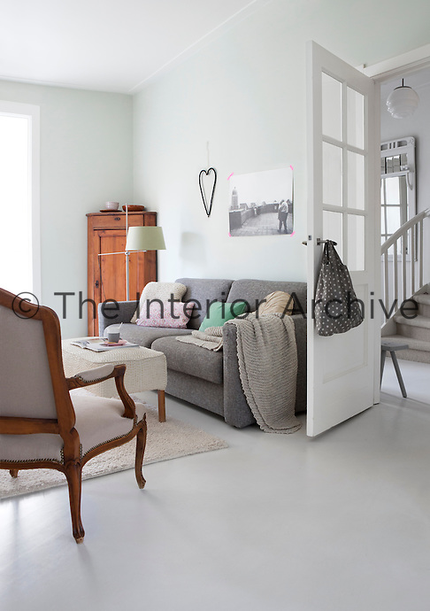 The simple living room is furnished with a mixture of family heirlooms and pieces from the couple's student days, such as the sofa, all of which are united by a sleek, polished grey floor