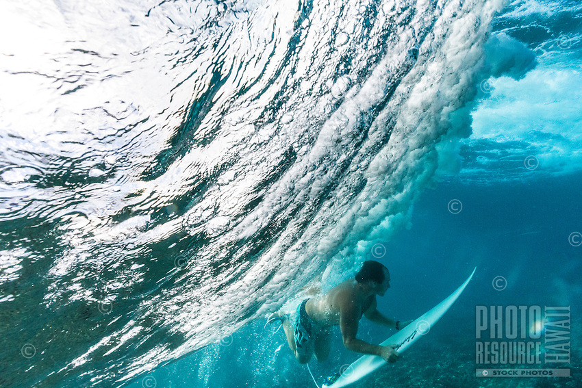 A surfer duck dives a big wave on the North Shore of O'ahu.