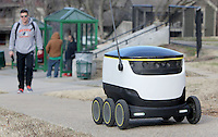 NWA Democrat-Gazette/DAVID GOTTSCHALK   Matt Sheppard, a senior at the University of Arkansas, monitors a 25 pound, six wheeled , self driving, delivery robot Monday, February 13, 2017, as it travels East on Center Street near the intersection of College Avenue in Fayetteville. Students in the McMillion Innovation Studio at the University of Arkansas are testing the Starship Technologies robot that was designed to deliver goods the last mile of a supply chain. The robot is scheduled to begin escorted deliveries next week.