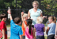 NWA Democrat-Gazette/DAVID GOTTSCHALK  Erica Rogers (left), with the Arkansas Tennis Association (cq), asks for a show of hands Thursday, September 10, 2015 from students at Vandergriff Elementary School, as they participate in a Free Play Day tennis clinic on the courts at the elementary school in Fayetteville. A joint use agreement grant between the U.S. Tennis Association and Vandergriff Elementary School has allowed the school to open the courts to the public after school hours on weekdays beginning at 4:00 p.m. and all day on the weekends.