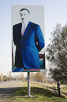 Azerbaijan. Gizil Hajili region. Gizil Hajili. A young man stands below a huge poster of the current President of Azerbaijan, Ilham  Aliyev (born December 24, 1961), who is the son of of the deceased political leader Heydar Aliyev. Ilham  Aliyev also functions as the head of the New Azerbaijan Party. Concrete road. © 2007 Didier Rue
