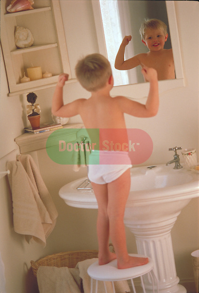 young boy standing on bathroom stool looking at reflecting in mirror