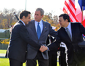 Camp David, MD - October 18, 2008 --   President Nicolas Sarkozy of France, who also serves as this year's rotating President of the European Union (EU), left, and President José Manuel Barroso of the European Commission (EC), right, shakes hands after making remarks as United States President George W. Bush, center, looks on at the Presidential Retreat near Thurmont, Maryland for talks on Saturday, October 18, 2008.  The two European leaders stopped at Camp David to meet with President Bush to discuss the economy on their way home from a summit in Canada to try to convince Bush to support a summit by year's end to try to reform the world financial system..Credit: Ron Sachs / Pool via CNP