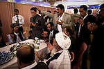 Hundreds of family members and friends - carefully divided between side's for men and women - attend a wedding at the lavish Mumtaz Majal wedding hall in Kabul. Glistening wedding halls dot the Kabul city scape and their attendance - which always includes large dinners and energetic dancing - is a mainstay of Kabuli social life. Here men from both sides of the family as well as elders and religious leaders come together to agree on the bride price and solemnize the wedding with verses from the Q'uran. The groom, stands center-left, a relative's hand on his head, as the mullah (seated to his left) recites from the Q'uran. The negotiated bride price was $15,000 - a princely sum to most in impoverished Afghanistan. Summer 2010.