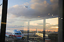 Airplanes and the Newark Liberty International Airport reflected on glass window at twilight. Newark, New Jersey, USA
