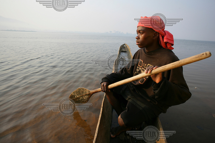 Young fisherman in a pirogue - dug out wooden canoe.