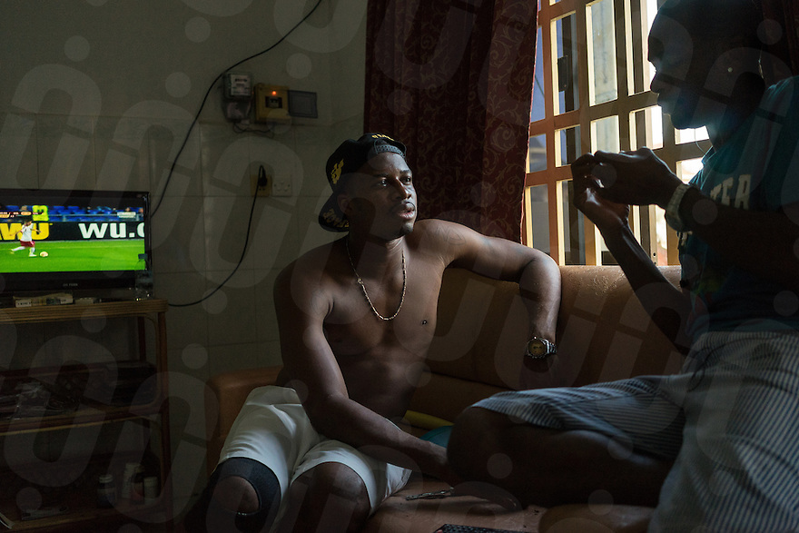 March 14, 2014 - Phnom Penh. Tomasz Esua hangs out at his flat with a fellow football player. Many African football players live together and rent accommodation near the Toul Sleng area in Phnom Penh. © Thomas Cristofoletti / Ruom.