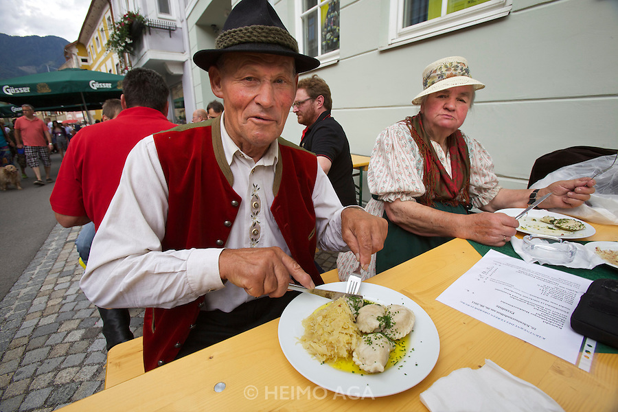 Kärntnernudelfest (Carinthian Dumplings Festival) in Oberdrauburg 2011. A local couple in festive dress enjoying their Kasnudeln.