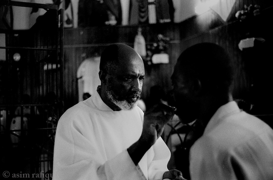 father jean-juste, friend of jean-bertrand aristide and possible Lavalas candidate in the upcoming elections, tends to his flock at the st.clair church in port au prince<br />